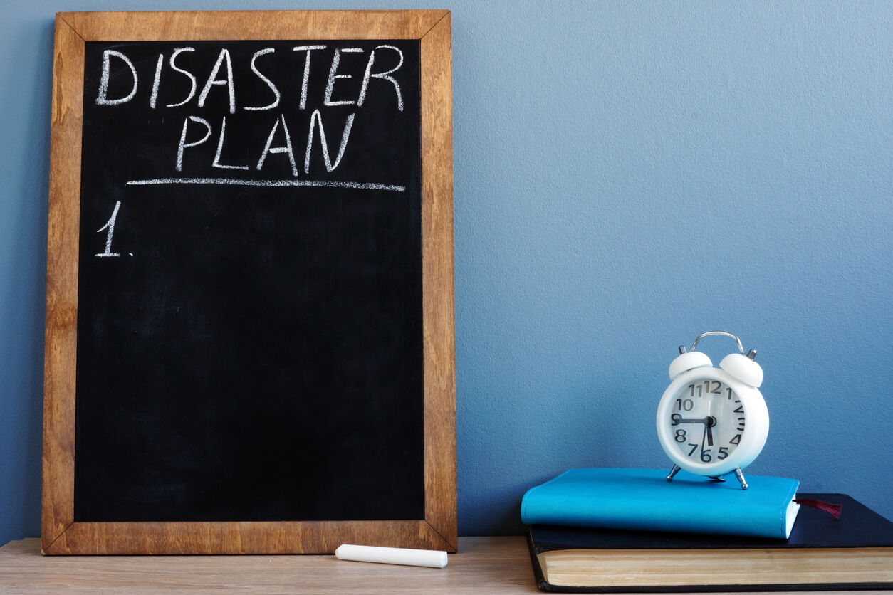 Chalkboard displaying 'Disaster Plan' sitting next to a white clock